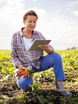 Mulher olhando seu tablet enquanto segura algumas cenouras
