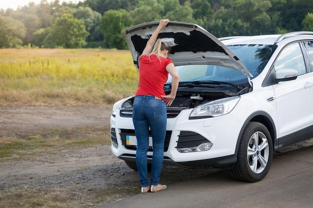 Mulher olhando sob o capô de um carro quebrado em offroad