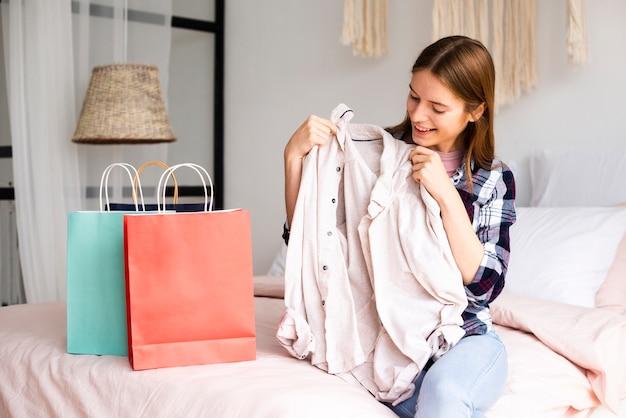 Mulher olhando uma camisa e sorrisos