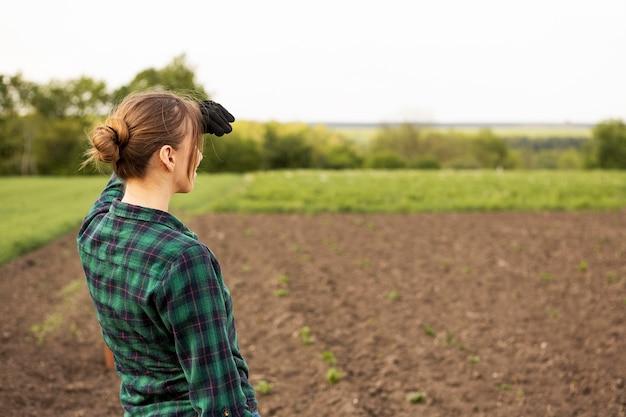 Mulher olhando uma terra de colheita
