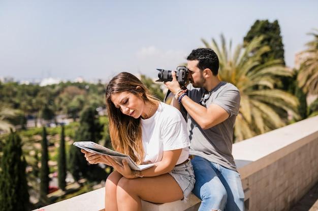 Mulher, olhar, mapa, sentando, com, dela, namorado, levando, fotografia, ligado, câmera, parque