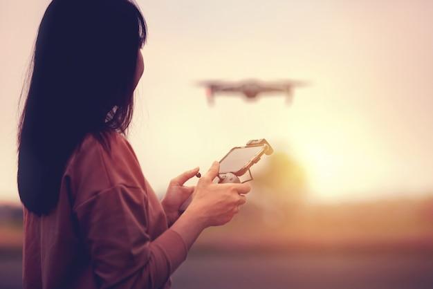 Mulher operando um drone com controle remoto ao pôr do sol