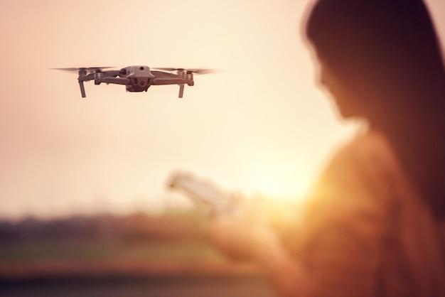 Mulher operando um drone com controle remoto.
