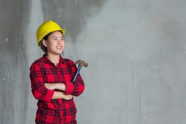 Mulher operária segurando um martelo no canteiro de obras