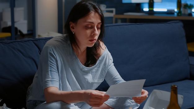 Mulher oprimida por muitos problemas ao ler aviso de despejo carta de demissão notificação de dívida ...
