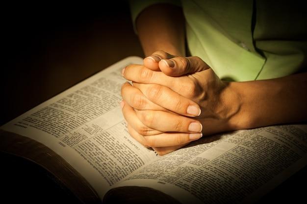 Mulher orando com a bíblia de perto
