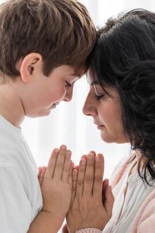 Mulher orando com seu filho
