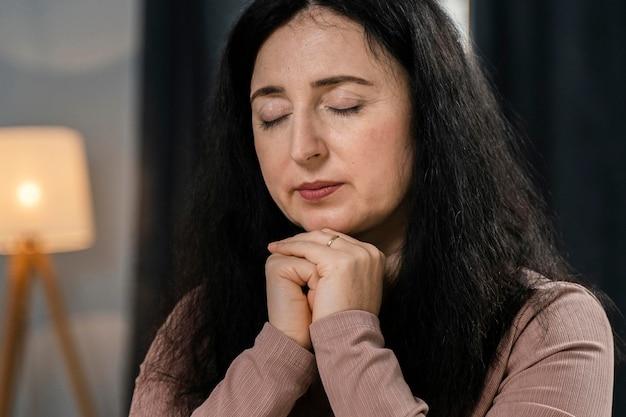 Mulher orando em casa