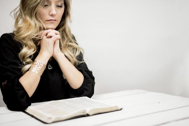 Mulher orando em frente à bíblia em uma mesa sob as luzes