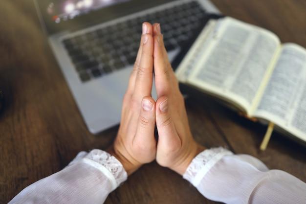 Mulher orando pela fé com computador laptop conceito online de serviços da igreja online