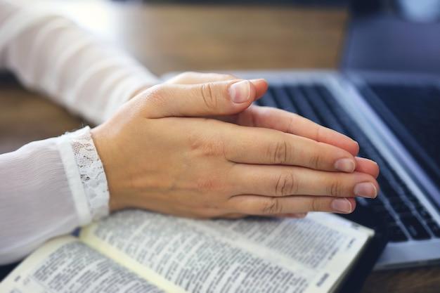 Mulher orando pela fé com o computador portátil, conceito on-line de serviços da igreja, conceito on-line de igreja em casa, espiritualidade e religião.