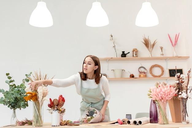 Mulher organizando buquês de flores em sua loja