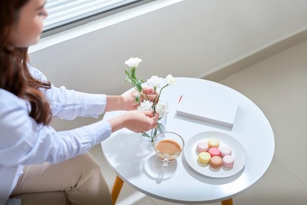 Mulher organizando flores de lisianthus em um vaso de vidro em casa.
