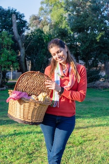 Mulher orgulhosa com a cesta cheia de alimentos saudáveis