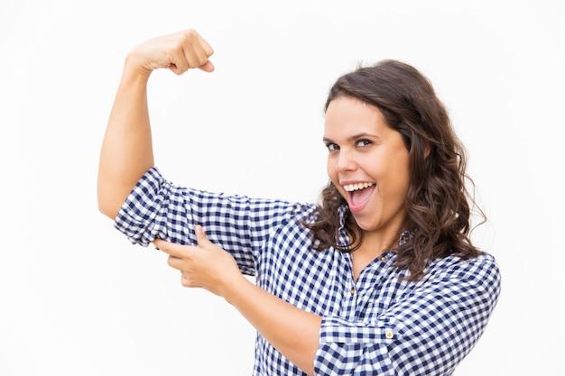 Mulher orgulhosa feliz mostrando o bíceps e sorrindo com a boca aberta