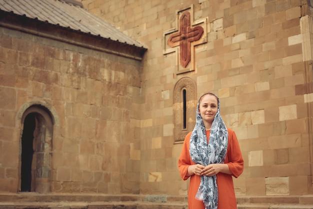 Mulher ortodoxa por uma antiga igreja cristã