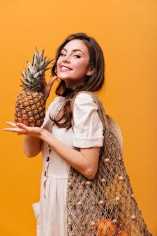 Mulher otimista com um grande saco eco segurando abacaxi e sorrindo em fundo laranja.