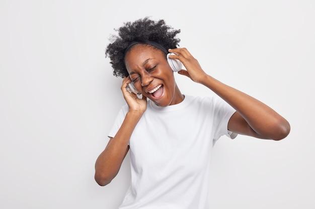 Mulher otimista de pele escura e cacheada inclina a cabeça, mantém as mãos em fones de ouvido estéreo e canta música