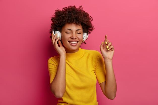 Mulher otimista de pele escura fecha os olhos e sorri em êxtase, goza de boa qualidade de som, usa fones de ouvido para ouvir música, dança despreocupada, vestida com roupas amarelas, isolada na parede rosa