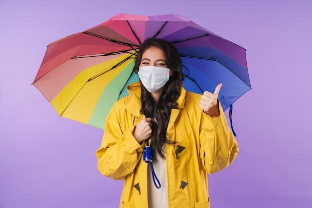 Mulher otimista positiva em capa de chuva amarela posando isolado sobre a parede roxa, segurando o guarda-chuva usando máscara médica aparecendo os polegares.
