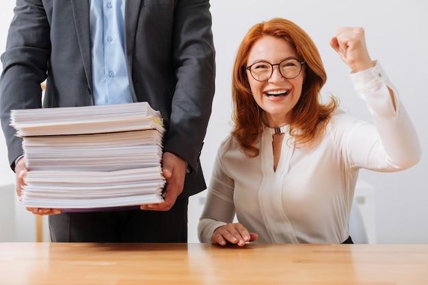 Mulher otimista, talentosa e trabalhadora, começando o dia no trabalho e recebendo muitas atribuições