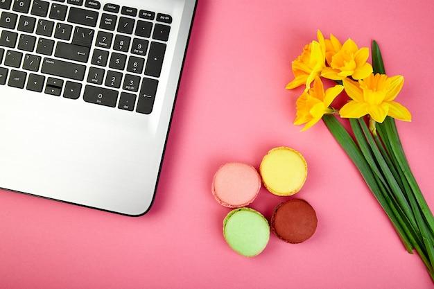 Mulher ou espaço de trabalho feminino com notebook, macarons e flores