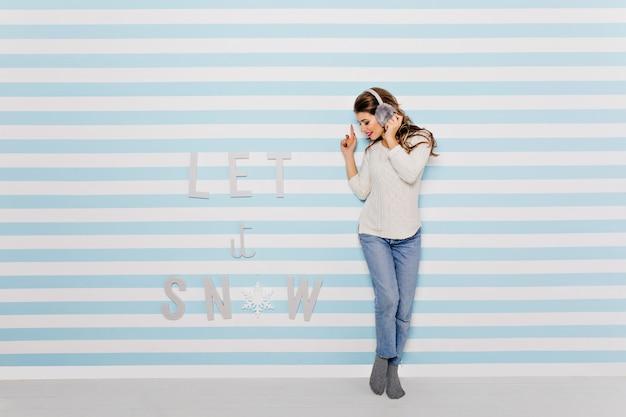 Mulher ouve boa música e pega o ritmo, posando com roupas fofas e fones de ouvido engraçados contra a parede azul