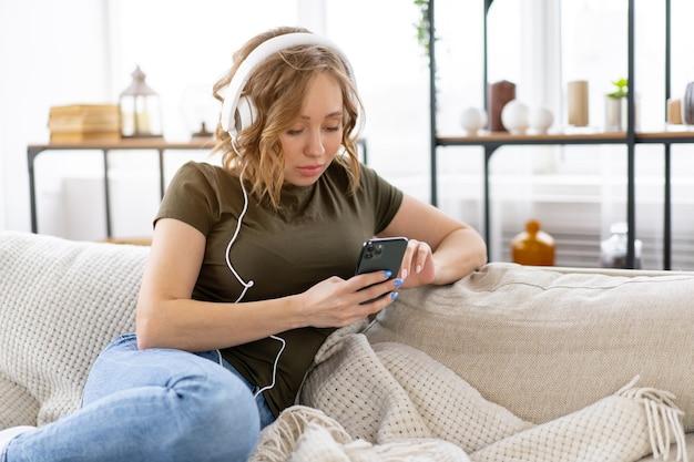 Mulher ouve música com fones de ouvido deitada no sofá, segurando o smartphone na mão