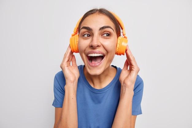 Mulher ouve música com fones de ouvido laranja vestida com uma camiseta casual risos otimista gosta de um bom som em branco