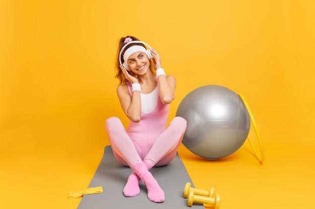 Mulher ouve música com fones de ouvido, senta-se com as pernas cruzadas no tapete de ginástica e treina ginástica com bambolê de bola suíça e halteres isolados em amarelo