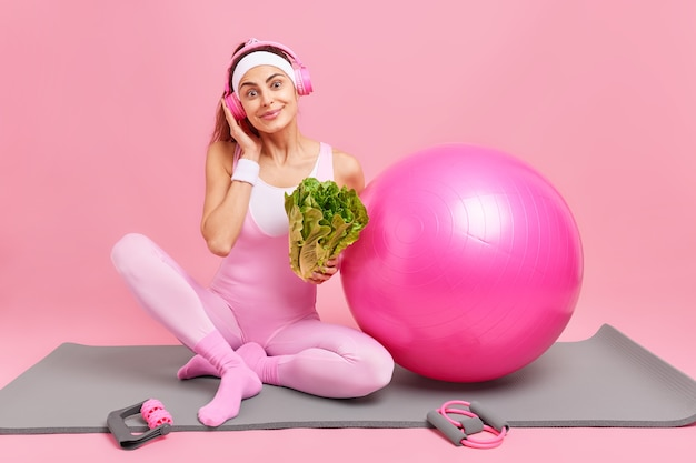 Mulher ouve música com fones de ouvido, usa bandana e roupas esportivas fazem poses de vegetais verdes frescos no tapete de ginástica com bola suíça