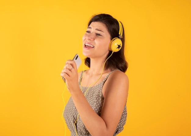Mulher ouvindo música com fones de ouvido e cantando, espaço amarelo