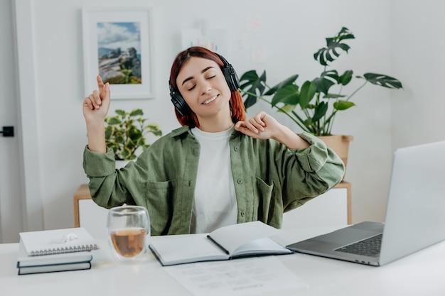Mulher ouvindo música com fones de ouvido sem fio conceito de descanso durante o estudo online em casa