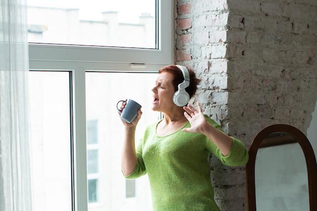 Mulher ouvindo música e cantando