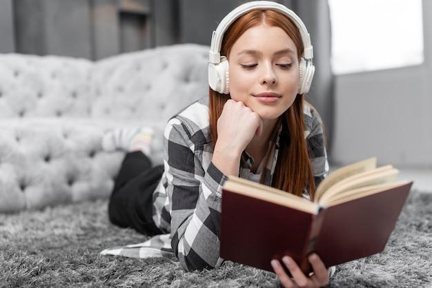 Mulher ouvindo música e lendo