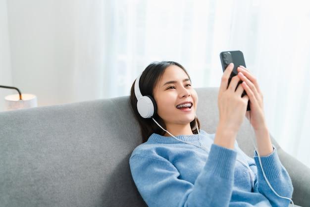 Mulher ouvindo música e usando o smartphone.