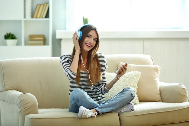 Mulher ouvindo música em fones de ouvido enquanto está sentada no sofá da sala