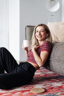 Mulher ouvindo música em fones de ouvido enquanto está sentada perto do sofá na sala de estar bebendo chá