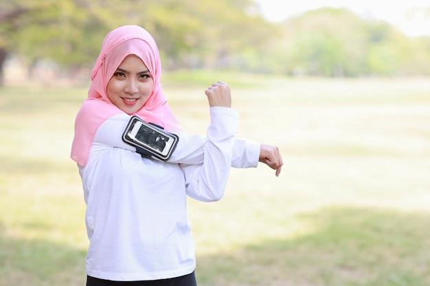 Mulher ouvindo música em fones de ouvido sem fio e celular enquanto se exercita ao ar livre