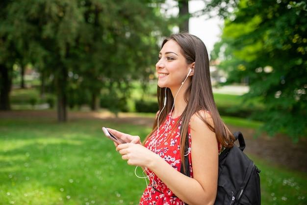 Mulher ouvindo música em um parque