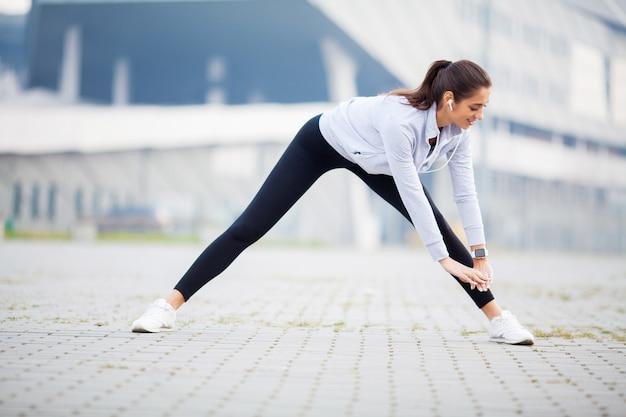 Mulher ouvindo música, fazendo exercícios de treino na rua