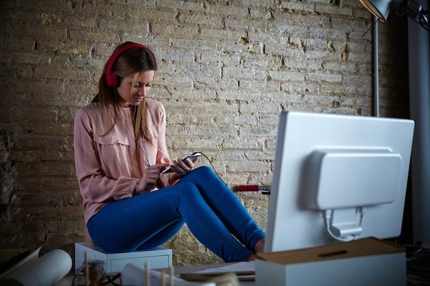 Mulher, ouvindo, música móvel, fones ouvido, em, escritório