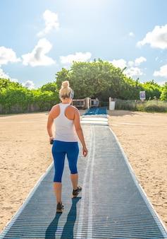Mulher ouvindo música no sportswear indo à praia em miami