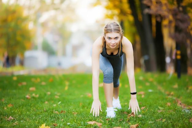 Mulher ouvindo música no telefone enquanto se exercita ao ar livre