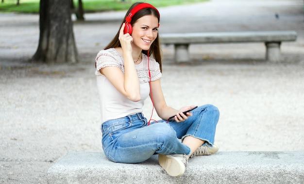 Mulher ouvindo música, sentado no banco de um parque