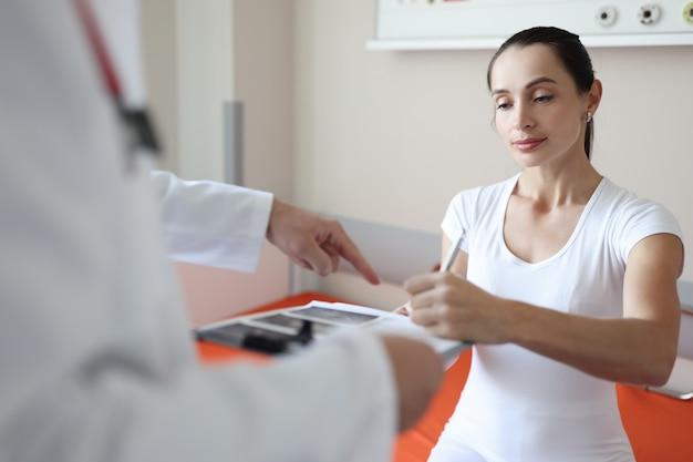 Mulher paciente assina documentos médicos na conclusão da consulta médica do conceito do tratado de medina