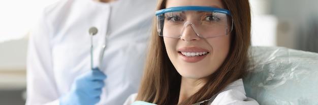 Mulher paciente com óculos de segurança sentada na cadeira odontológica perto do médico