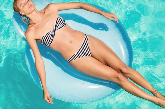 Mulher pacífica no lilo na piscina