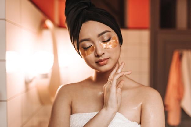 Mulher pacificada depois do banho em poses de toalha com tapa-olhos