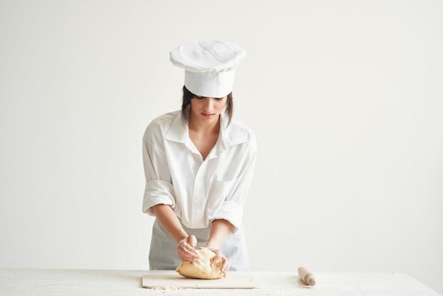 Mulher padeiro chef uniforme fazendo massa de pizza e massas. foto de alta qualidade